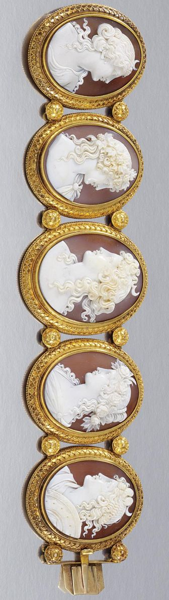 GOLD AND SHELL CAMEO BRACELET, 1860S.  Designed as five graduated oval shell cameos depicting the profiles of Diana and Bacchantes, encased within textured bead and scroll work frames, length approximately 178mm, fitted case.