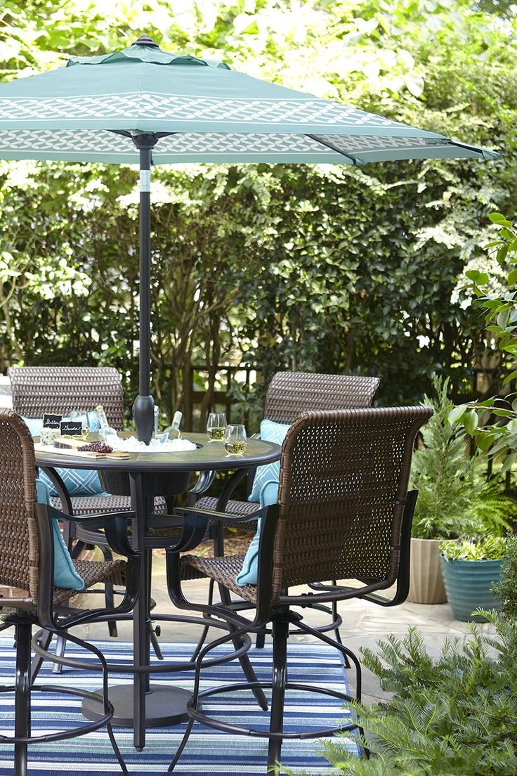 A Bar Height Patio Table Features An Umbrella For Shady Downtime Outdoors.  Stay Extra
