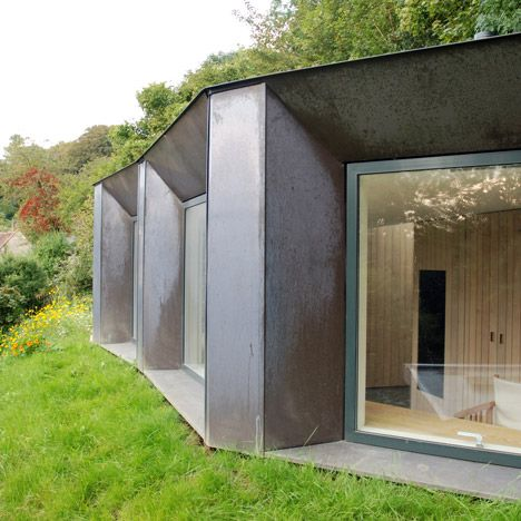 Embedded in the garden of an English countryside cottage, this small studio with a green roof and rusty copper walls creates a spot for deer-watching