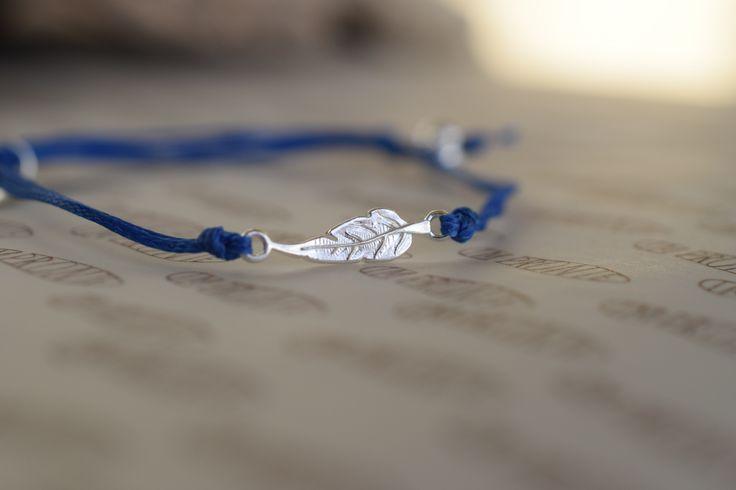 PEŘÍČKO-Náramek vyroben z modré voskované šňůry s malým pírkem z chirurgické oceli, velikosti 0,5 cm. Dozdoben medailonkem Impronte.  Rády vám vyrobíme náramek z drahých kamenů dle Vašeho přání hodící se k tomuto náramku.