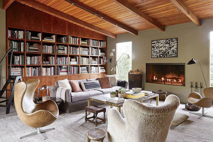 wall of bookshelves w/ ;ibrary stairs, mix modern & trad furniture, like the fireplace, mid-century modern living room/library ... the Birdhouse, Ellen Degeneres house in Hollywood Hills