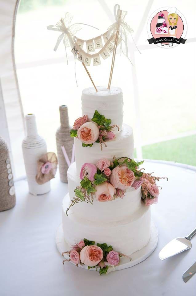 Rustic buttercream wedding cake with fresh flowers.