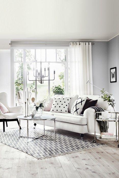 Ljusgrå väggar, ljust golv, vit soffa. (Hampton 3-sits soffa i tyg Dover natur från Mio.) Vardagsrum.