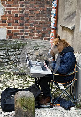 A street entertainer dressed up as a horse, playing on a keyboard. Cracow Krakow Poland, winter 2016.