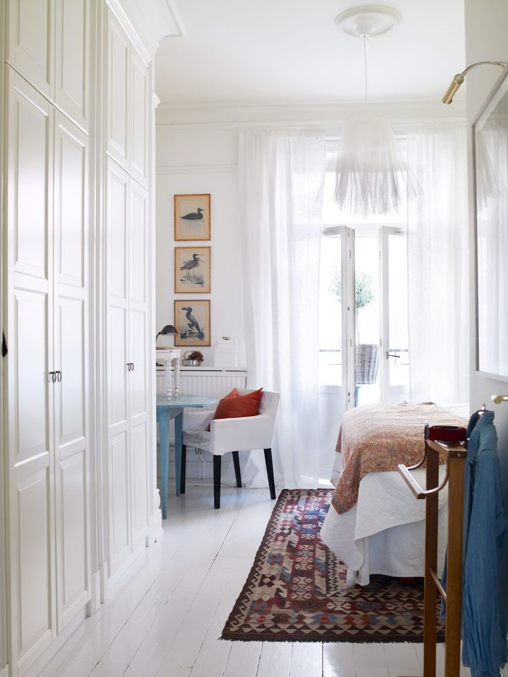 Swedish white bedroom with wood floors painted in very light gray. The French doors draped in white sheer fabric open to garden.