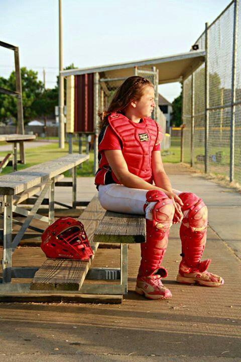 Softball player but instead a regular helmet behind her and her holding her glove between her legs