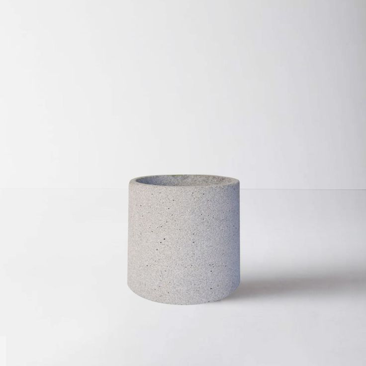Zakkia Grey Concrete Medium Planter: A grey concrete planter which has a multitude of uses. This grey concrete planter looks equally at home in the kitchen, bathroom, bedroom or living area. As well as being a stylish way to display a plant or flowers it can also be used for storing kitchen utensils or cutlery on a kitchen bench top or pens and pencils in the office. Concrete home accessories have a cool, clean raw appeal. This planter is no exception and is part of a range of products…