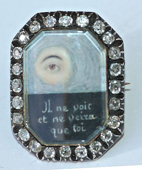 Georgian Eye Miniature | An eye miniature brooch, circa 1800, set gold and silver and in a surround of diamonds. The watercolour on ivory miniature depicts an eye in clouds and beneath it is a most unusual motto and poignant motto : il ne voit et ne veira que toi [he sees only you and he'll have eyes for you only].