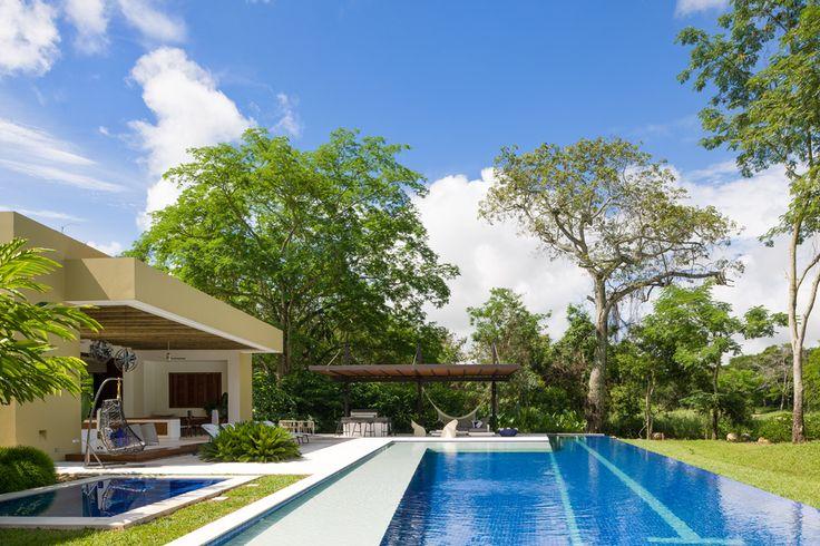 El espacio de la zona social y una pérgola que da sombra a la parrilla de los asados enmarcan el área de la piscina de borde infinito y el jacuzzi, enchapados en mosaico de vidrio azul.