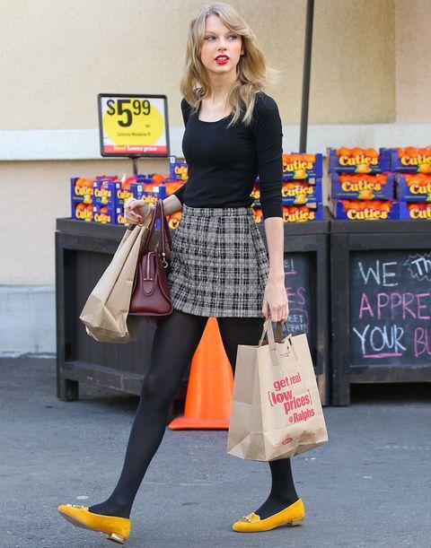 Para hacer la compra la cantante Taylor Swift confía en una minifalda de cuadros, camiseta y medias negras, bailarinas mostaza y bolso burgundy.