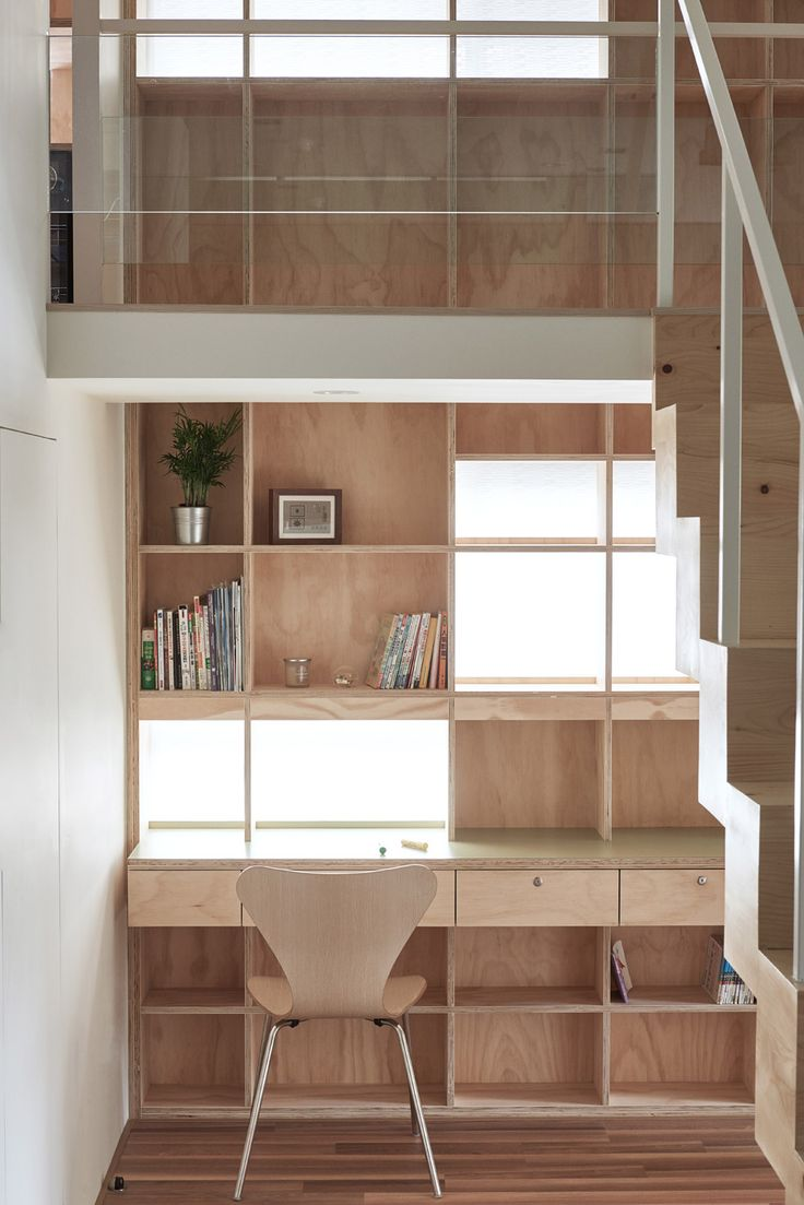 A double-storey bookcase covers the wall of this apartment, integrating shelves, window and a desk