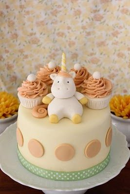 Chubby unicorn reclining on cupcakes, circled by things that look like nilla wafers... heart is melting