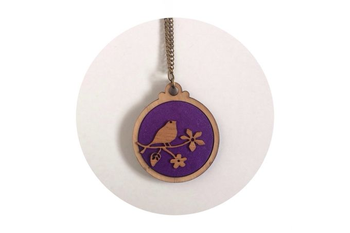 Maple Plywood circle pendant with purple fabric inlay. Bird on twig veneer detail