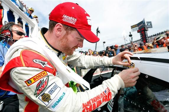 Dale Earnhardt Jr putting winning sticker on race car at Pocono.