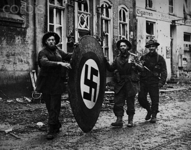 Three Canadian soldiers roll a large round swastika sign down a muddy street. The Canadian troops are helping to dismantle local Nazi Party headquarters in Nijmegen, the Netherlands. February 1945.