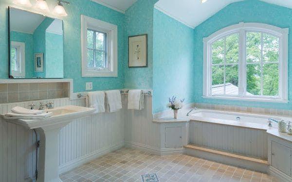 El baño pintado y decorado en aguamarina y blanco y ventanales sin cortinas dejando entrar a la luz natural