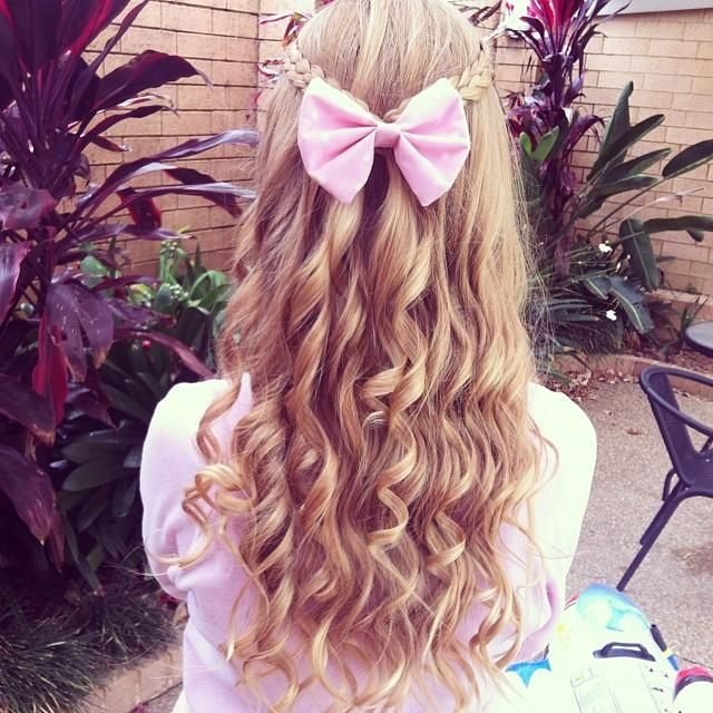 Curly blond hair with pink bow.