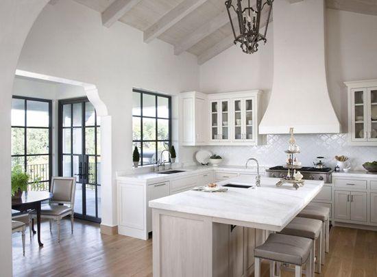 All white kitchen design with wrought iron lantern-style pendant light