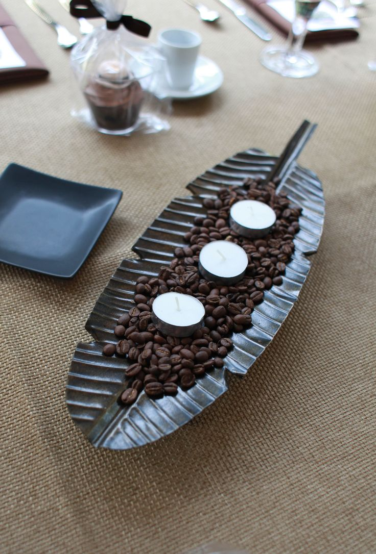 Havana table decorations....metal palm leaves, coffee beans and votive candles...