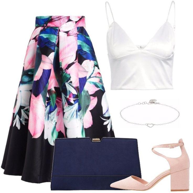 L'outfit è composto da una gonna a campana a fantasia floreale, un top con scollo a V profondo, un paio di tacchi rosa e da una pochette in fintapelle.