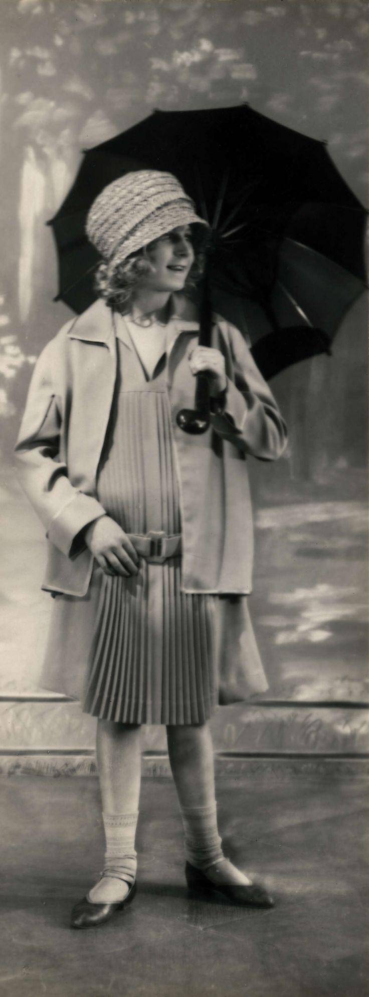 Mode. Kinderkleding. Een  meisje gekleed in een geplooide jurk met daaroverheen en driekwart mantel. Ze heeft een strohoed op en houdt een paraplu vast. . Duitsland, 1926.