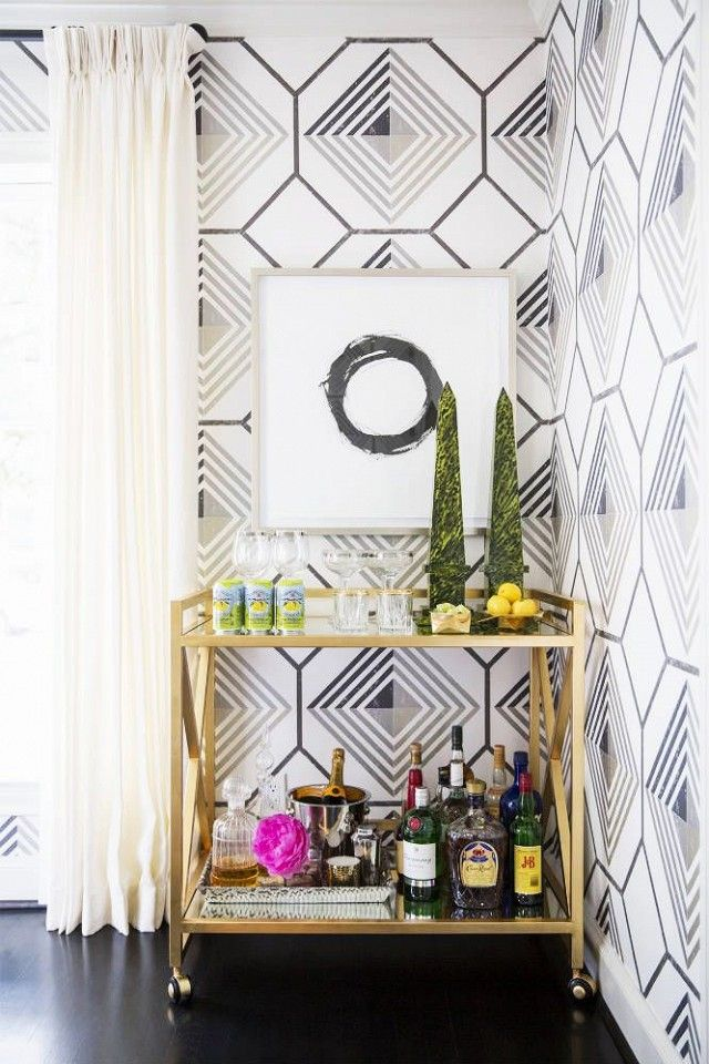 Living space corner with geometric wallpaper, and a gold bar cart