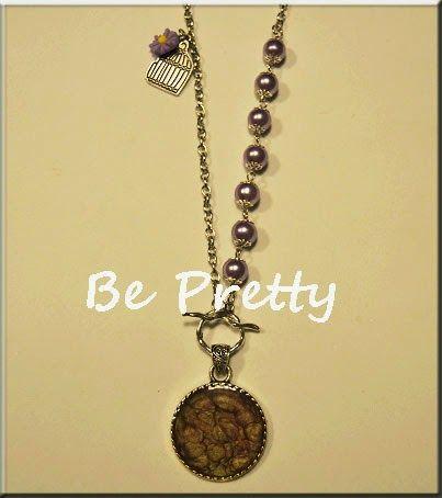 Colar comprido, cor prata, com pérolas de vidro lilás e medalhão pintado à mão, em tons lilás e prata.