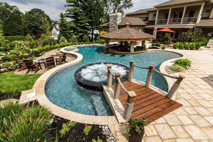 This freeform pool features a firepit swim up bar and a for Pool and spa show usa