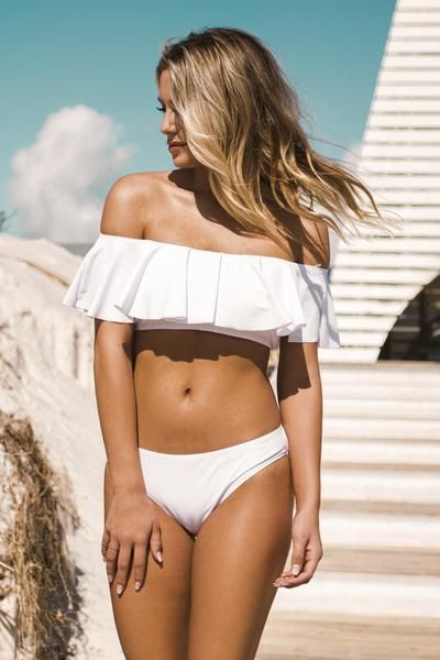 A white bandeau bikini featuring ruffled overlay, off the shoulder details with sleeves, built in padding, and lining White bikini bottoms with lining Material
