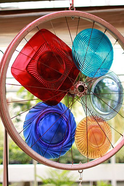 An old bicycle wheel and colourful glass plates = light catcher.        Gloucestershire Resource Centre http://www.grcltd.org/home-resource-centre/