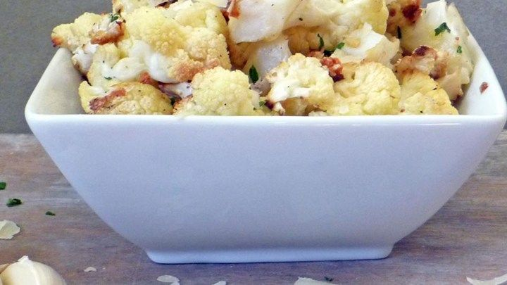 Tender roasted cauliflower tossed in olive oil and garlic is topped with Parmesan and cheese and broiled until golden brown.