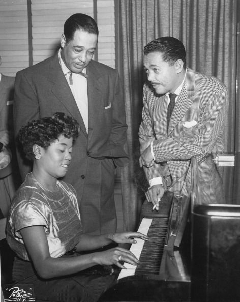 """Sarah Vaughan plays the piano as Duke Ellington and Billy Eckstine look on, circa 1950. The Newark, NJ-born Ms. Vaughan studied piano as a child and went on to win first prize at the Apollo Theater's famous Amateur Night competition. BillyEckstine was in the audience that night and before long, Ms. Vaughan would sing with Mr. Eckstine in his band. Her recording of """"The Duke Ellington Songbook, Vol. 1 and 2,"""" is still unmatched for its beauty and brilliance. Photo by Gilles Pet"""