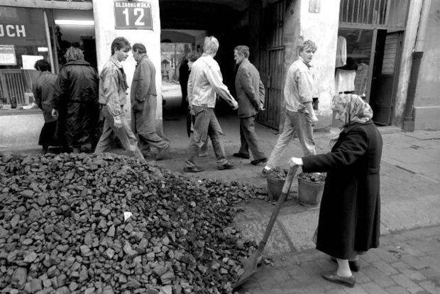 W PRL-u niełatwo było zdobyć węgiel. Na zdjęciu starsza kobieta ładuje kupiony węgiel do wiader, Warszawa, ul. Ząbkowska, obrazek z roku 1989