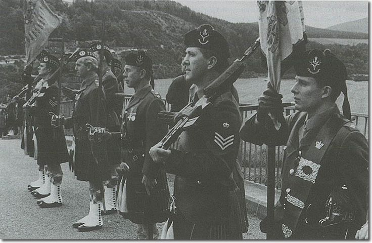 The Colours of the Queen's Own Highlanders (nearest the camera) and the Gordons are carried by junior officers and guarded by Colour sergeants with SA80s. The Commanding Officers of the two regiments stand together between the Colour Parties. Amalgamation 1994