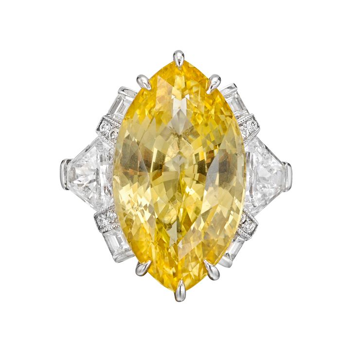 Raymond C. Yard Marquise-Shaped Yellow sapphire ring in platinum with diamond side stones. Marquise-shaped yellow sapphire weighing 12.46 carats, surrounded by two calf's head-shaped diamonds weighing 1.22 total carats, four baguette-cut diamonds weighing 0.25 total carats and eight round-cut diamonds weighing 0.07 total carats.