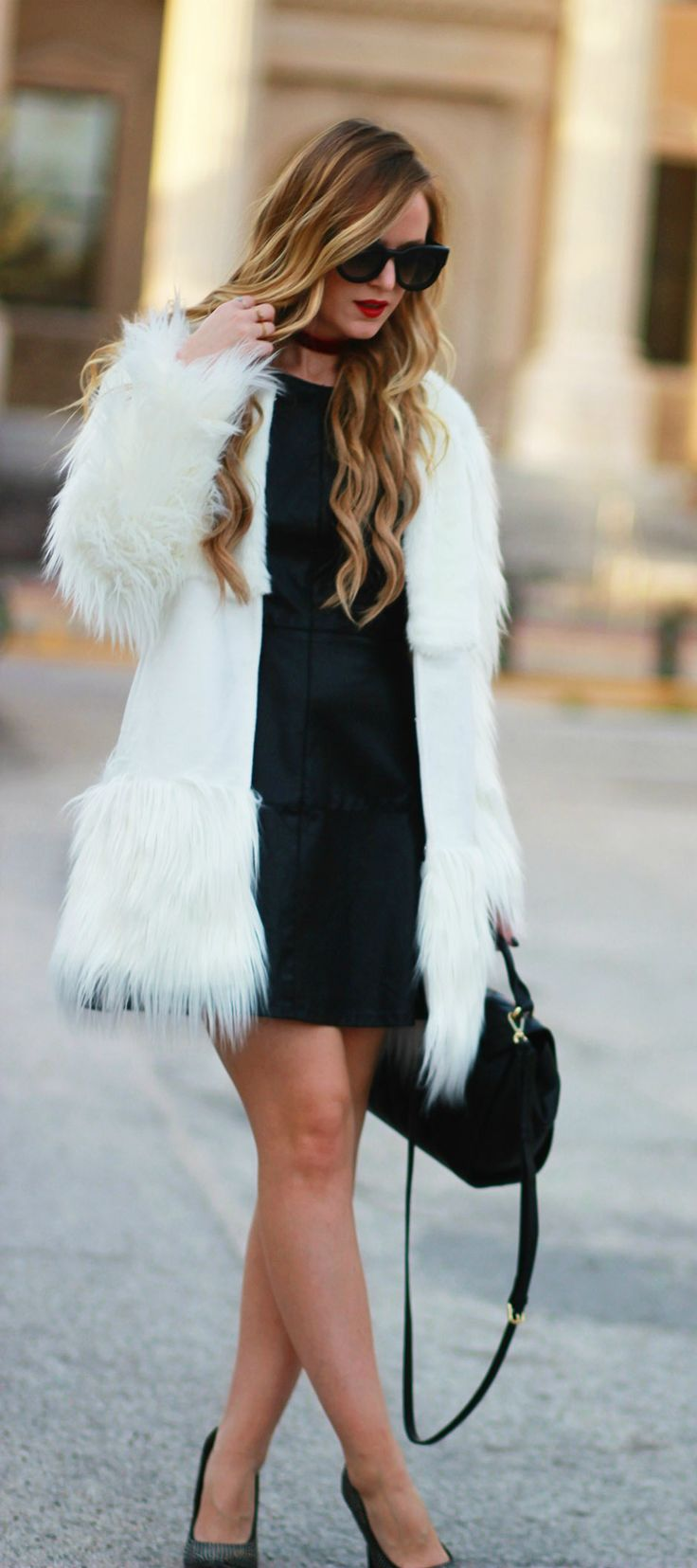 Winter date night outfit styled with a leather mini dress, white fur coat, and sparkly heels