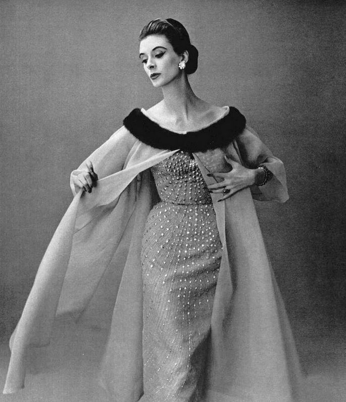 1956 Rachel Fitzgerald in a wispy orange organza coat, flared and trimmed with mink collar, worn over orange chiffon dress embroidered in gold, by Jean Dessès