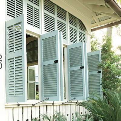 """Operable shutters also flank the French doors inside the porch. """"I love using shutters with adjustable slats because even when closed, the slats can be positioned to let air circulate,"""" architect Jim Strickland says."""
