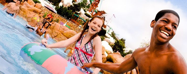 2 smiling teens enjoying the water at Blizzard Beach while adults look on at Disney's Blizzard Beach Water Park