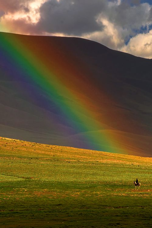 Horse riding near the Rainbow in Mongolia, it has more than 250 sunny days a year.