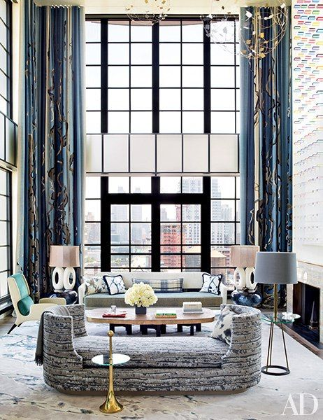 In the double-height living room, a Deniot-designed daybed covered in a Métaphores fabric and accented by an Hermès throw is joined by several vintage pieces, including a FontanaArte side table (in the foreground), an Ado Chale cocktail table, and an Edward Wormley sofa