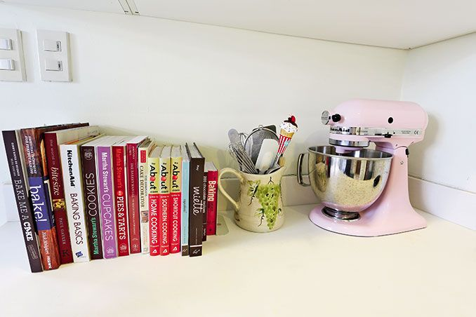 Since Nikki enjoys baking, this corner holds a special place in her heart! It has a pink mixer, baking tools in a mug, and a row of cookbooks.