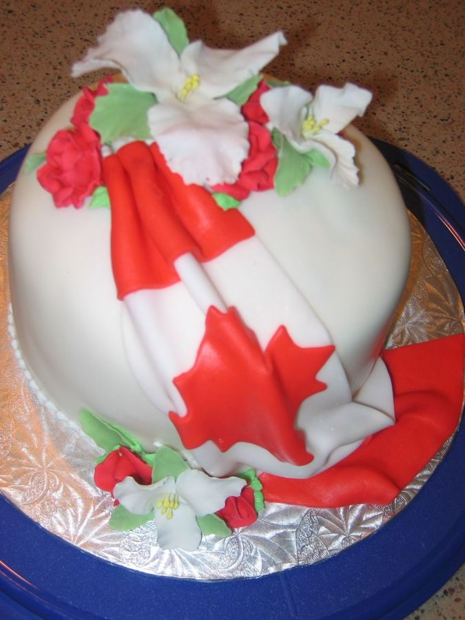 This Canada Day cake has a fondant overlay of the Canadian flag and Gum Paste trilliums (The Capital of Canada is in Ottawa, Ontario - the t...
