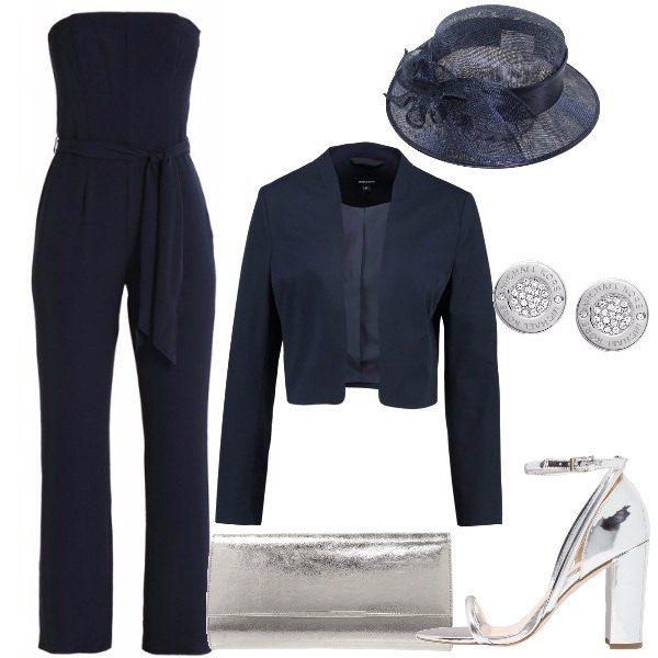 L'outfit è composto da una jumpsuit blu navy senza spalline e con cintura in vita da indossare con un blazer senza bottoni ton sur ton . Il look si completa con il cappello in tessuto sisal con fiocco, gli orecchini Micheal Kors e la pochette silver come i sandali con tacco.
