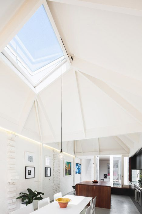 Two angular skylights funnel daylight into a kitchen and dining area at the rear of this renovated house in Sydney.