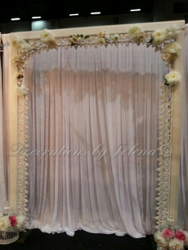 Custom vintage wedding ceremony arch with silk flowers and draping