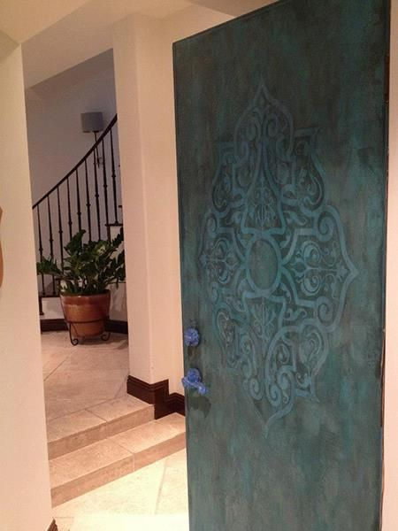 An Eastern Center Stencil (EasCen103) from Modello® Designs within a copper oxidized finish on a door by Nichole Blackburn of Celadon Studio and Fine Art.