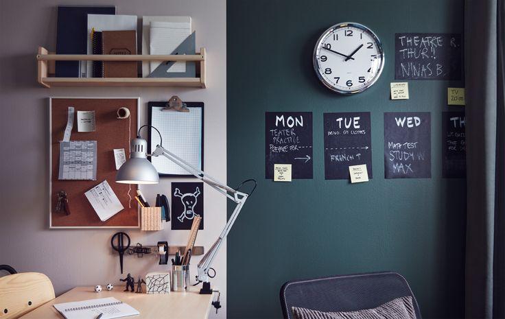 Arbeidsplassen på et tenåringsrom med skrivebord, arbeidslampe, hyller, skriveplate, klokke, oppslagstavle og ukeplan på veggen