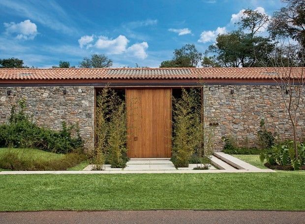 Fachada | A porta de entrada, com vidros nas laterais, é emoldurada por bambus hachikus com forração de evólvulos. O muro é formado por pedras Moledo (Foto: Leonardo Finotti e Luis Gomes)