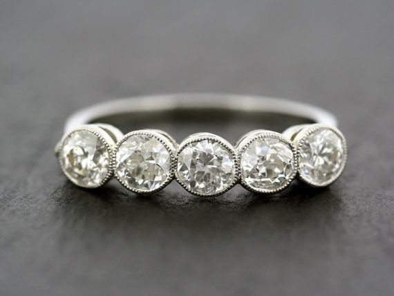 A variation on a classic style of Edwardian diamond anniversary ring. This ring is made from platinum and set with five old brilliant-cut diamonds in millegrain-edge collet settings. The diamonds are of varying sizes, but present a uniform appearance on the finger. A perfect ring for a diamond anniversary gift, or even an unusual and unique antique engagement ring.  Diamonds: - There are five old brilliant-cut diamonds of varying sizes. We would estimate the total weight of all the diamonds…